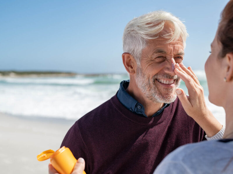 Portrait of cheerful old man looking at his mature wife applying sunscreen on nose. Senior husband enjoying vacation with woman while applying sunscreen on face at beach. Middle aged retired couple applying suntan lotion at sea with copy space.